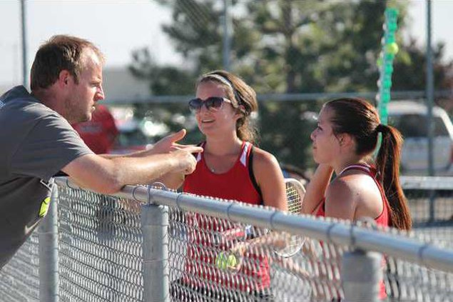Coach Dustin Wheeler discusses strategies with Rachel Carpenter and Rebecca Dawson