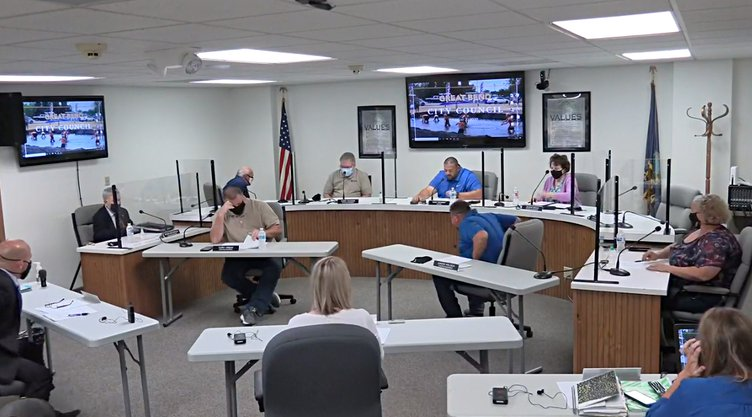 city council meeting with shields and masks