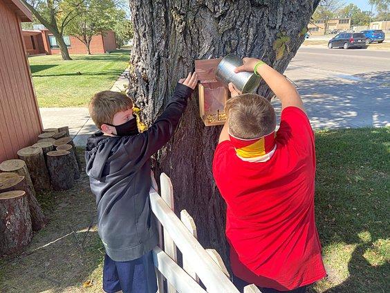 Kids filling squirrel feeder
